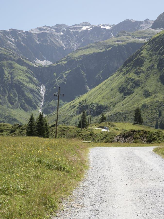 Sceniczna Alpejska skalista wysokogórska dolina Sportgastein w lecie z rzędem linie energetyczne i elektryczność słup zdjęcia stock