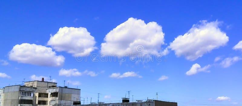Sceniczne chmury na Głębokim niebieskiego nieba tle nad Nieociosanym budynkiem mieszkaniowym betonów panel na Jaskrawym letnim dn zdjęcie stock