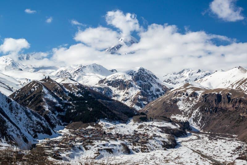 Scenicznej zimy panoramiczny widok od tarasu na Kazbek górze i Gergeti trójcy kościół w Kazbegi fotografia stock