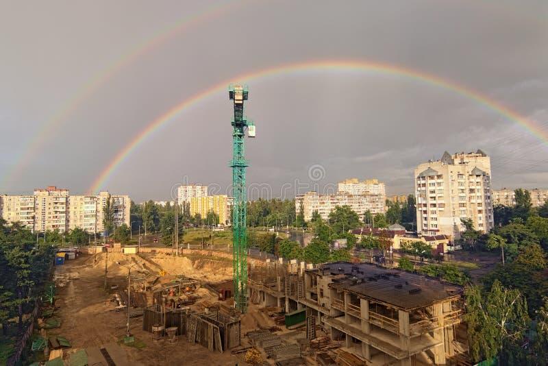 Sceniczny krajobrazowy widok miasto po deszczu Dwoista tęcza przeciw chmurnemu niebu Budowa z wysokim żurawiem w dużym mieście zdjęcie stock
