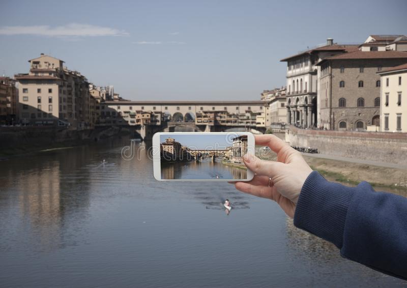 Sceniczny widok dziejowy centrum Florencja most i budynki stara grodzka ręka z smartphone na ekranie, z czego obraz royalty free