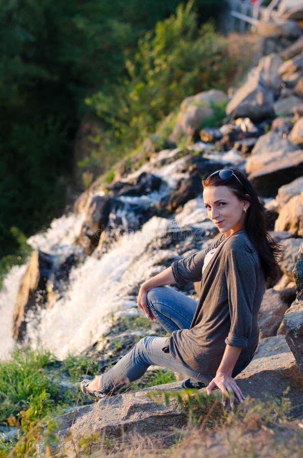Sceniczny widok, dziewczyny obsiadanie na skałach blisko siklawy zdjęcia stock