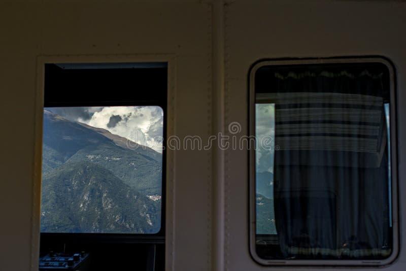 Sceniczny widok jachtu kabinowy okno na górach w Włochy na Jeziornym Como zdjęcie stock
