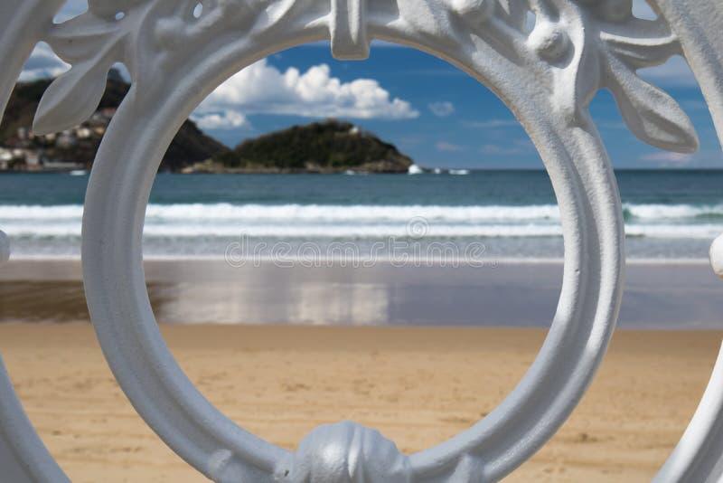Sceniczny widok na San Sebastian plaży z wzgórza monte igueldo i Santa Clara wyspie przez ornamentacyjnej bielu żelaza ogrodzenia zdjęcie stock