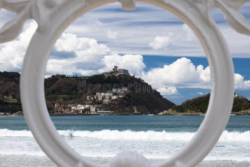 Sceniczny widok na San Sebastian plaży z wzgórza monte igueldo i Santa Clara wyspie przez ornamentacyjnej bielu żelaza ogrodzenia obrazy stock