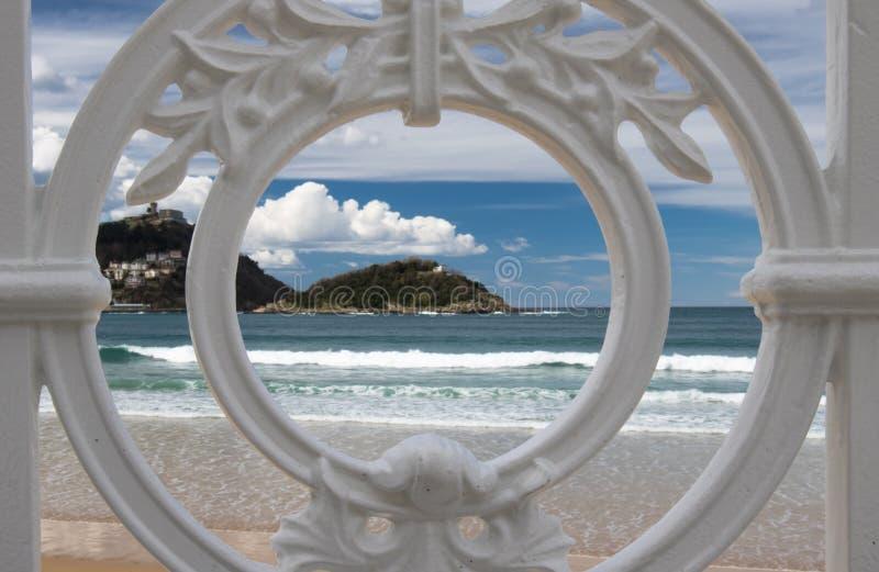Sceniczny widok na San Sebastian plaży z wzgórza monte igueldo i Santa Clara wyspie przez ornamentacyjnej bielu żelaza ogrodzenia obraz royalty free