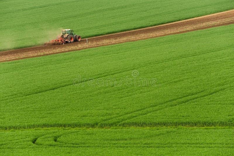Sceniczny widok Nowożytny Uprawia ziemię ciągnik Który oranie zieleni pole Rolnictwa Ciągnikowy Uprawowy Pszeniczny pole I Tworzy obrazy stock
