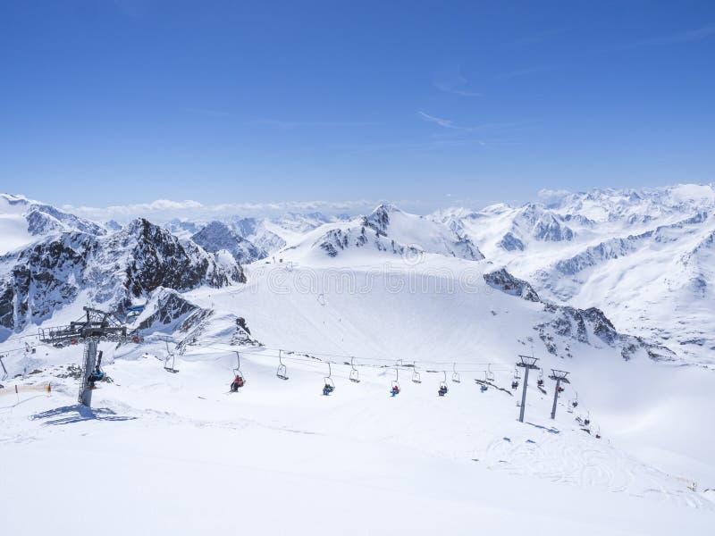 Sceniczny widok od wierzchołka Wildspitz na zima krajobrazie z śniegiem zakrywał halnych skłony, pistes i narciarki na krześle zdjęcie stock