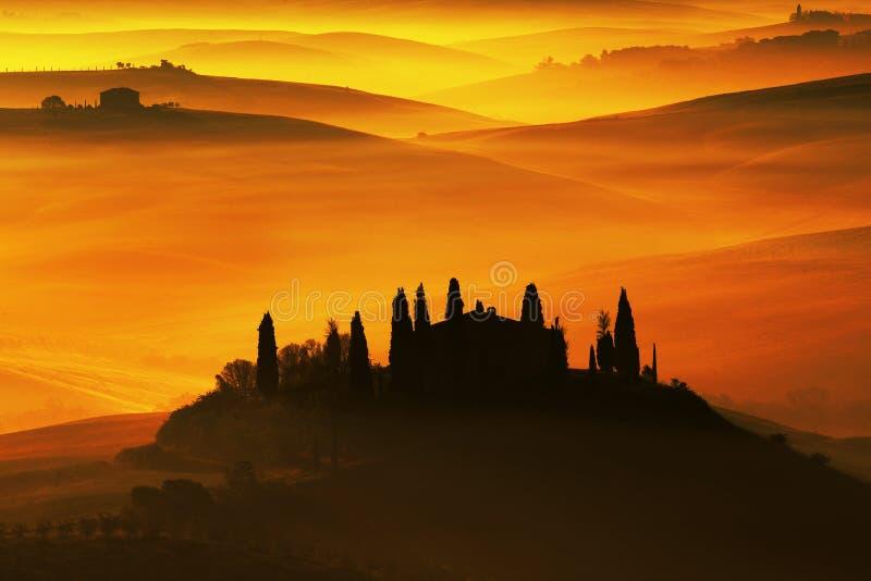 Sceniczny widok typowy Tuscany krajobraz, dom z wzgórzami podczas pomarańczowego zmierzchu, Włochy obraz stock
