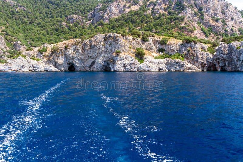 Sceniczny widok wyspy na morzu egejskim Unikalni cienie morze i skały zakrywający z sosnami obraz stock