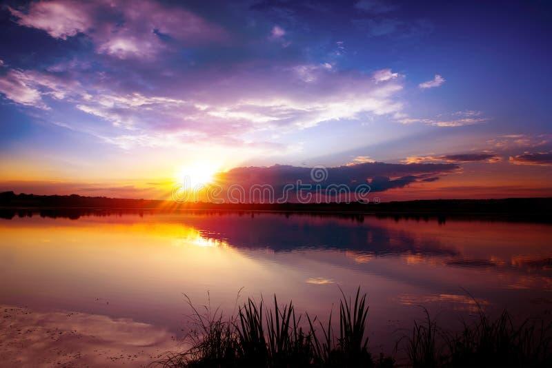 Scenisk aftonsolnedgång på sjön med molniga himlar royaltyfri foto