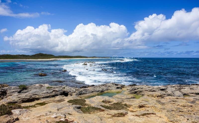 Scenisk karibisk Seascape med blåa molnig himmel och Rocky Coast i förgrund arkivfoto