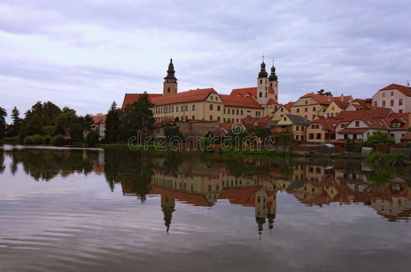Scenisk morgonsikt av medeltida Telc på soluppgång Byggnader reflekteras i vattnet royaltyfri fotografi