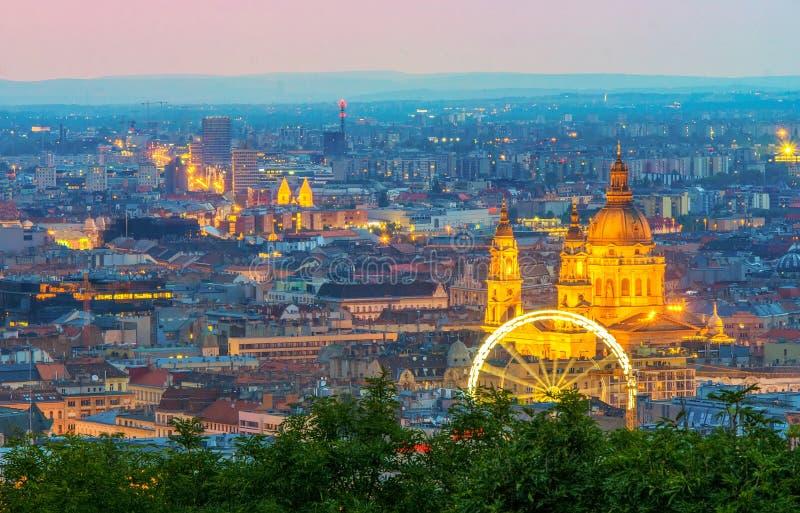 Scenisk nattscape av St Stephen & x27; s-basilika, ferrishjul och plågaområde i Budapest, Ungern arkivbilder