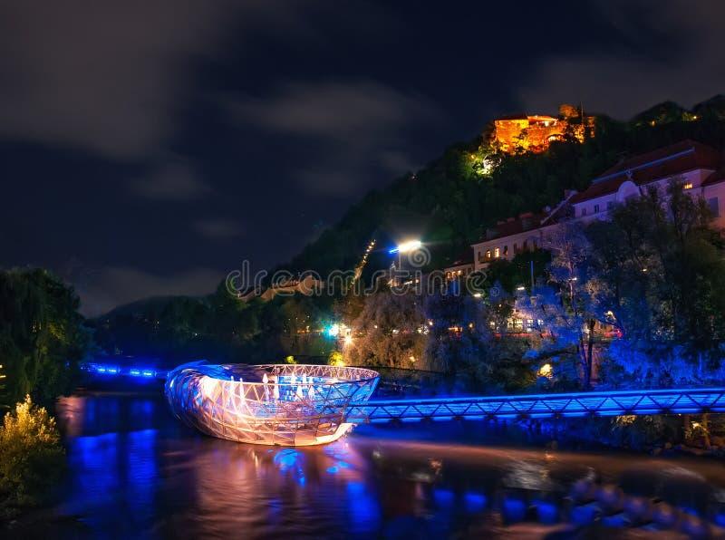 Scenisk nightscape av den Murinsel bron på flodMur och den upplysta slotten i Graz, Österrike arkivbild
