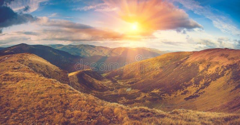 Scenisk panoramautsikt av berg Höstlandskap: sjö och färgrika kullar på solnedgången arkivfoto