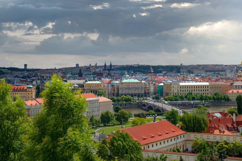Scenisk panoramautsikt av den historiska mitten av Prague, broar och den Vlatva floden på en molnig dag royaltyfria bilder