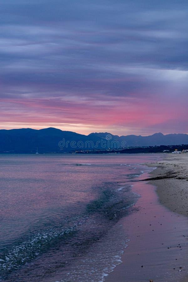 Scenisk r?d soluppg?ng ?ver kustlinjen med den sandiga stranden och klart havsvatten i den Alcamo marina, liten stad i Sicilien,  arkivbilder