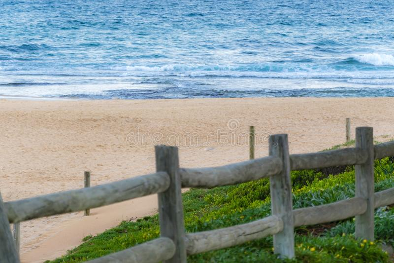 Scenisk sikt av den övergav sandiga stranden och havvågor, trästaket i förgrund arkivbild