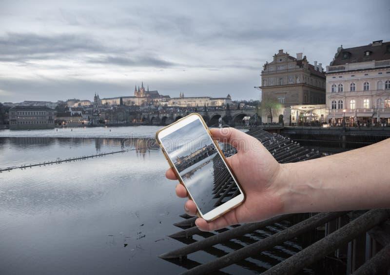 Scenisk sikt av den historiska mitten Prague, den Charles bron och byggnader av den gamla stadhanden med en smartphone, på skärme royaltyfria foton