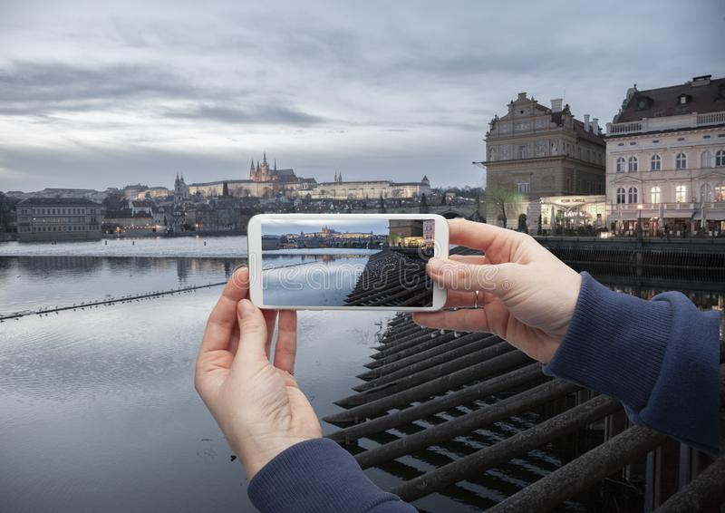 Scenisk sikt av den historiska mitten Prague, den Charles bron och byggnader av den gamla stadhanden med en smartphone, på skärme arkivfoto