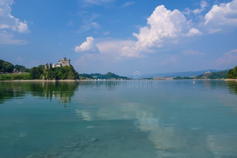 Scenisk sikt av den Niedzica slotten och den konstgjorda Czorsztynskie sjön i sydliga Polen royaltyfri foto