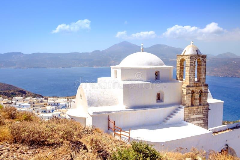 Scenisk sikt av den traditionell grekisk cycladic kyrkan, byn och se arkivfoton