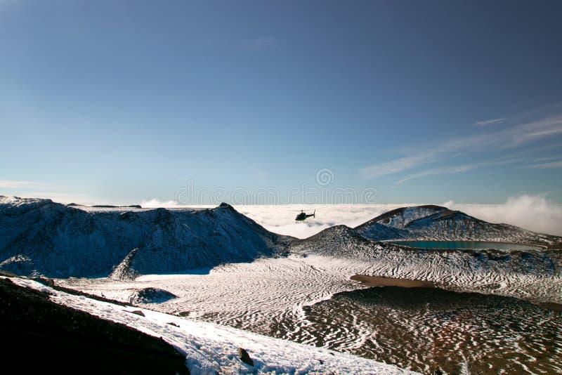Scenisk sikt av det snöig landskapet för lösa berg med den djupblå sjön ovanför molnen och räddningsaktionhelikoptern som sparar  royaltyfri fotografi