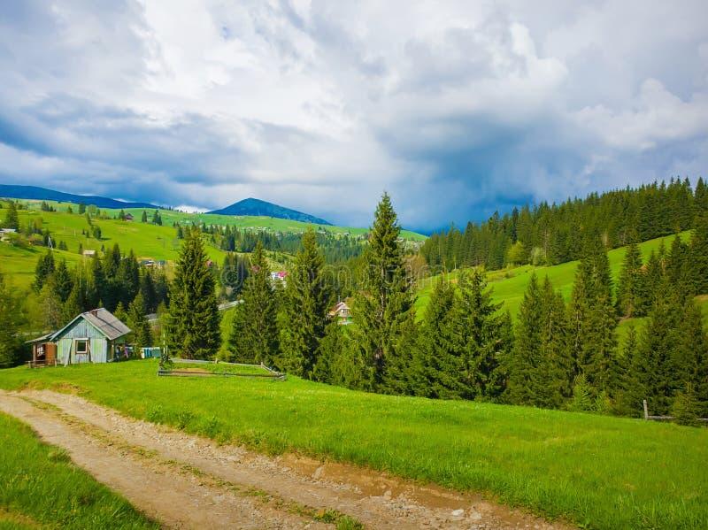 Scenisk sikt av en cuontry väg som leder till en gammal by av träkabiner på kullarna av Carpathians Solig vårdag med gräsplan royaltyfria foton