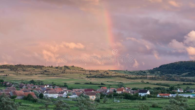 Scenisk sikt av en regnbåge över en rumänsk by efter sommarregn, på solnedgången arkivfoton