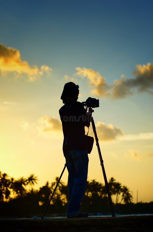 Scenisk sikt av fotografsilhoutte p? solnedg?ngbakgrunden royaltyfri fotografi