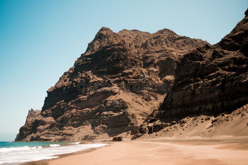 Scenisk sikt av gui-gui-stranden i den grancanaria ön i Spanien med spektakulärt berglandskap och klar blå himmel och sandigt arkivfoto