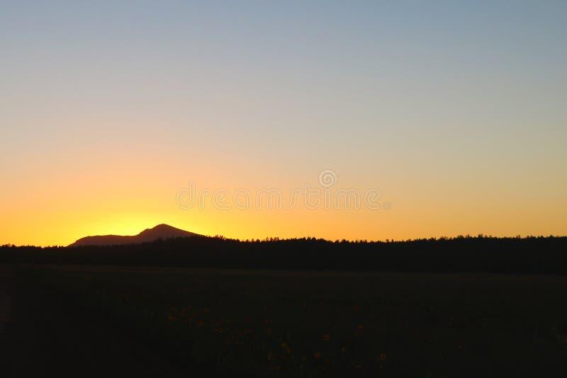 Scenisk sikt av konturberg mot orange himmel arkivfoto