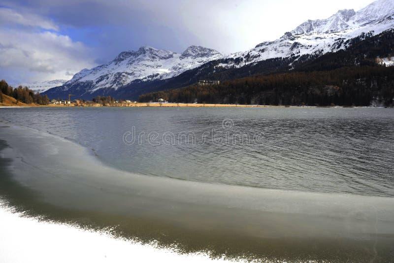 Scenisk sikt av landskapet för vintersnöberg och den djupfrysta sjön i de schweiziska fjällängarna i Engadin arkivbilder