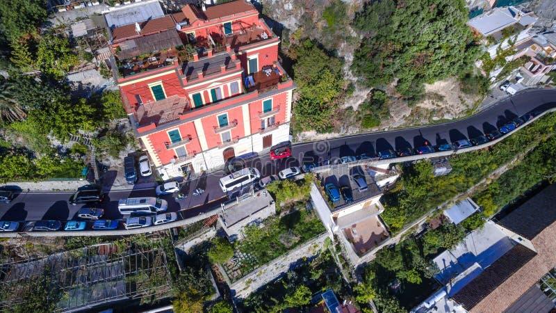Scenisk sikt av Positano, den härliga medelhavs- byn på Amalfi, Italien den smala vägen och hög trafik i bergen som byggs royaltyfri bild