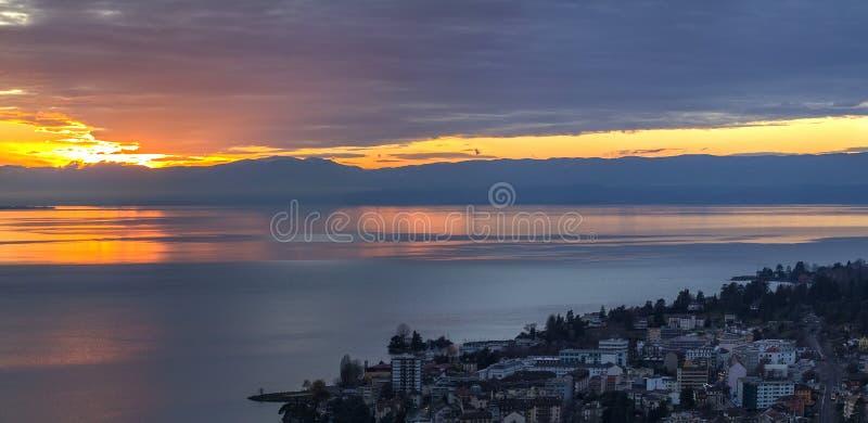 Scenisk sikt av solnedgången över Leman sjön med gul himmel med moln och fjällängberg i bakgrund, Montreux, Schweiz arkivfoton
