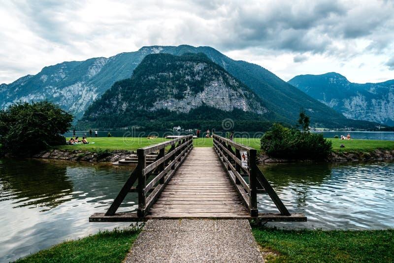 Scenisk sikt av träbron i sjön mot berg arkivfoton