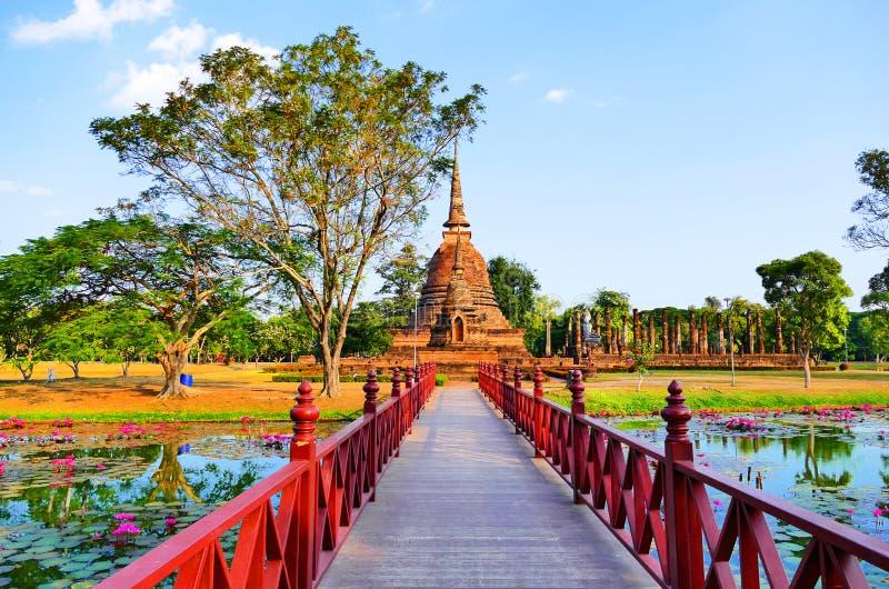 Scenisk sikt för härligt landskap som en röd bro som korsar Traphang-Trakuan sjön till den forntida buddistiska templet, fördärva arkivfoto