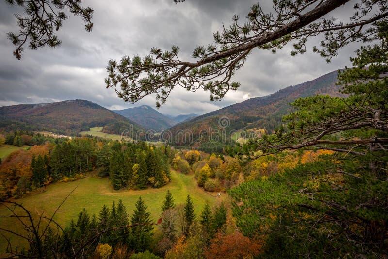 Scenisk sikt från överkant av Hausstein till den gröna dalen av Muggendorf med den färgrika höstskogen och dramatisk molnig himme royaltyfria bilder