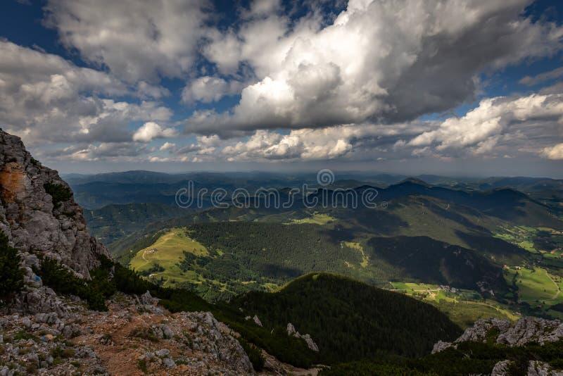 Scenisk sikt med mörkt, blått, molnigt, himmel från den Rax platån, Schneeberg massiv, på dalen med den Puchberg byn royaltyfri foto