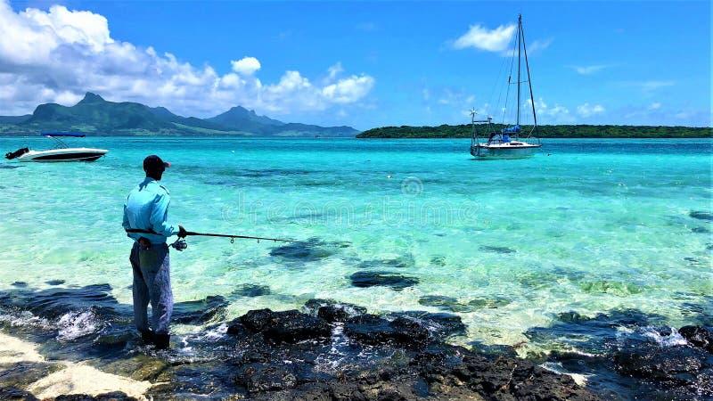 Scenisk sikt på den blåa fjärdlagun Mauritius med fisheren royaltyfri bild