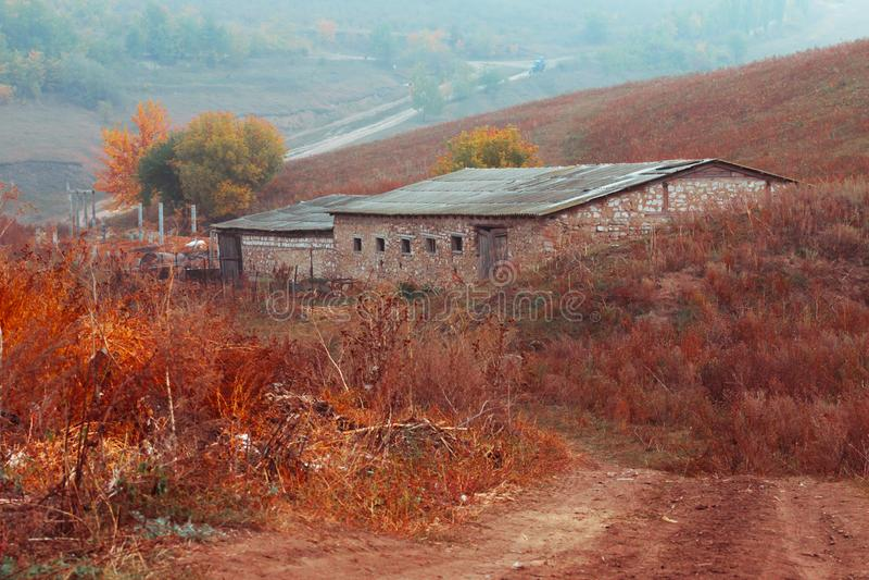 Scenisk sikt på den lantliga vägen i förgrund, ladugårdbyggnad på kullen arkivfoto