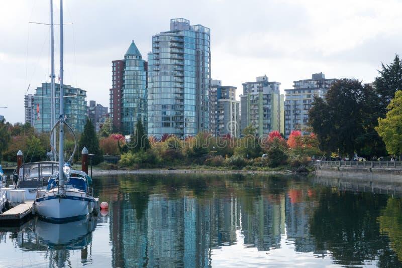 Scenisk sjö och skyskrapor med nedgånglövverk, den färgrika röda apelsinen och gulingsidor i höst, Kanada Vancouver, F. KR. royaltyfri fotografi