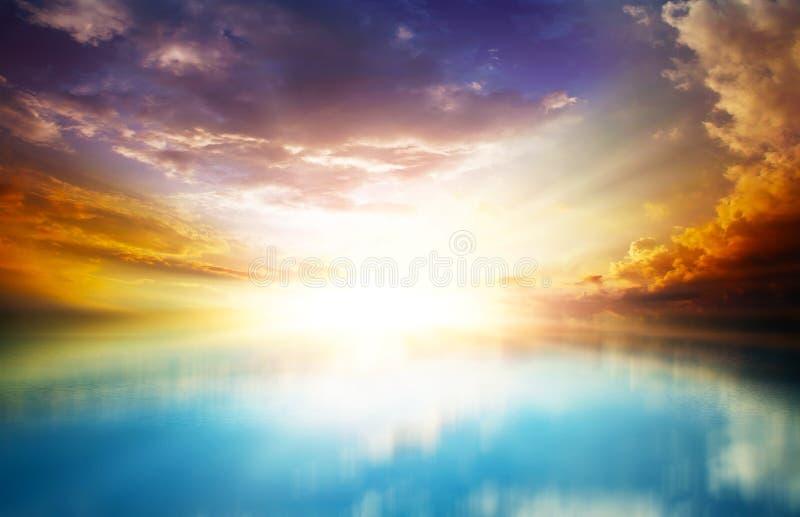 Scenisk solnedgång i det öppna havet med molniga himlar royaltyfri fotografi