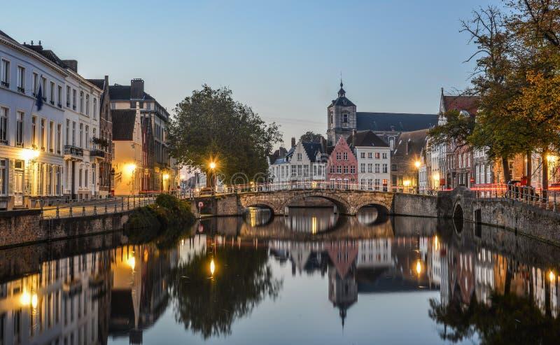 Scenisk stadssikt av den Bruges kanalen på natten arkivbilder