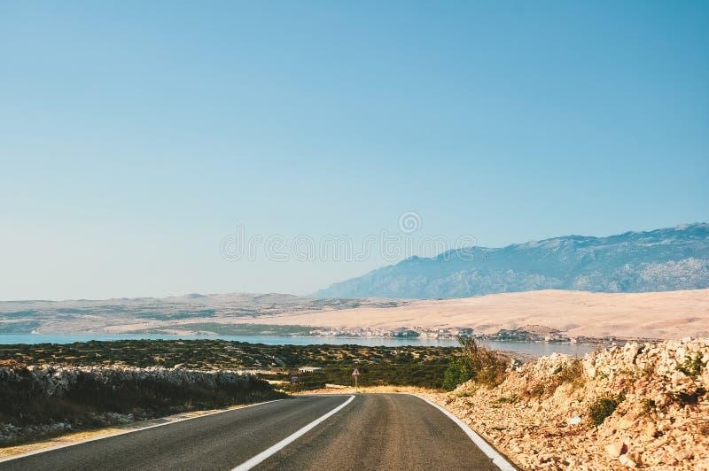 Scenisk väg vid havet i Kroatien som leder till Pag, på ön, med berg i bakgrunden arkivfoton