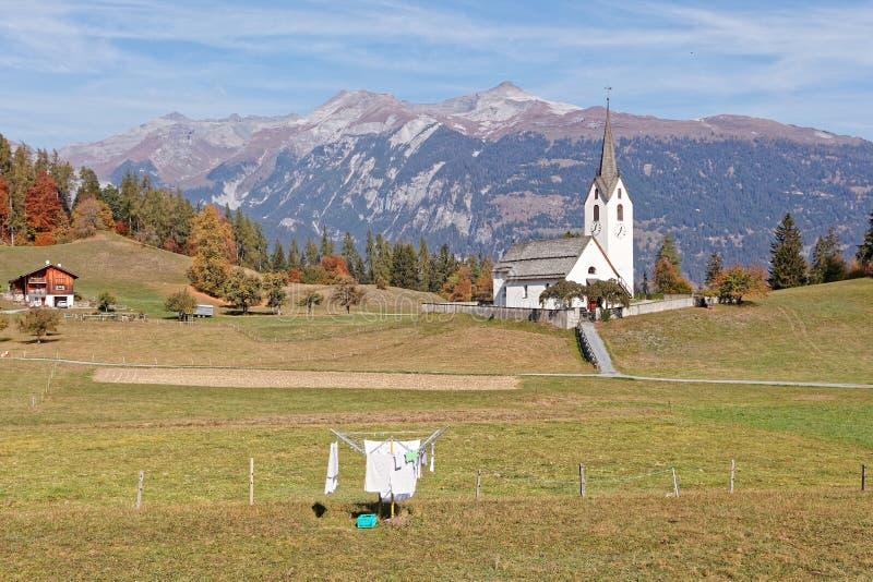 Sceniska bergsikter av den Ringelspitz massiven, tvätteri, kyrka i bergbyn Versam, Ruinaulta arkivbild
