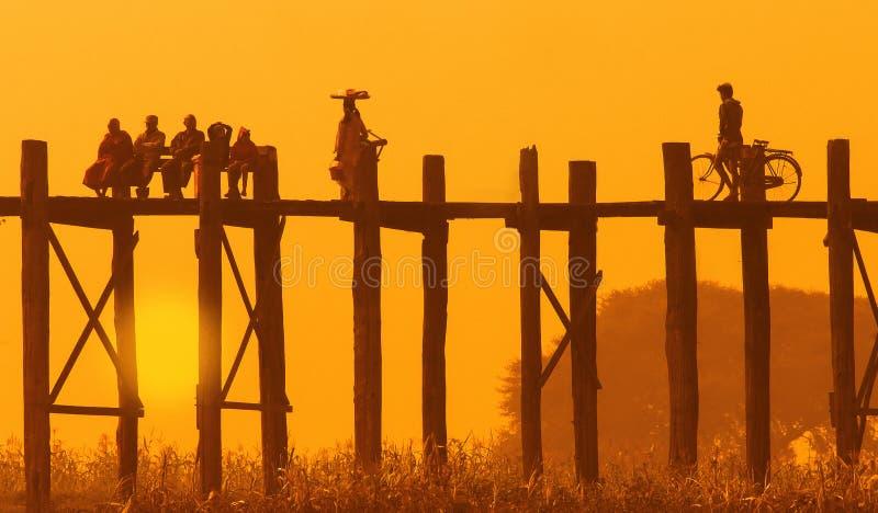 Sceniskt landskap av bron för U Bein på solnedgången med konturer av folk Förorter av Mandalay, Myanmar royaltyfri fotografi