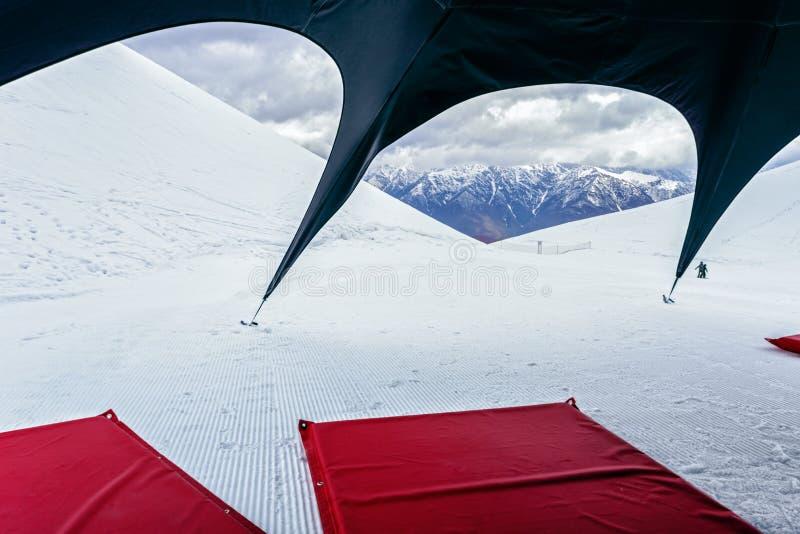 Sceniskt landskap för vinterbergmaximum med röda madrasser på snö under det svarta tältet Campa aktiviteter och fritid på skidar  royaltyfri foto