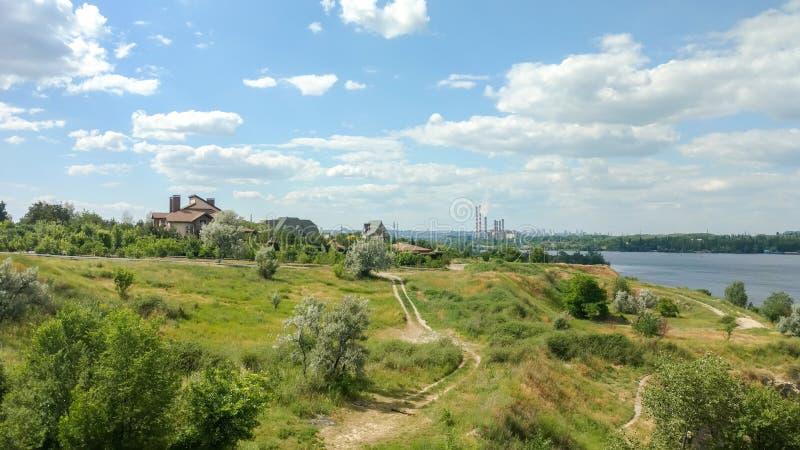 Sceniskt landskap som förbiser kullen med banor, en flod, landshus, blå molnig himmel och röka rör arkivfoto